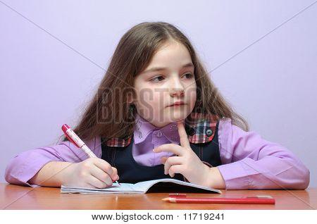 Thinking Little School Girl Doing Homeworks At Desk