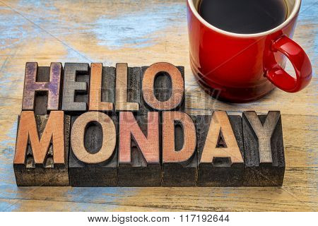 Hello Monday  word abstract in vintage letterpress wood type printing blocks stained by color inks with a cup of coffee
