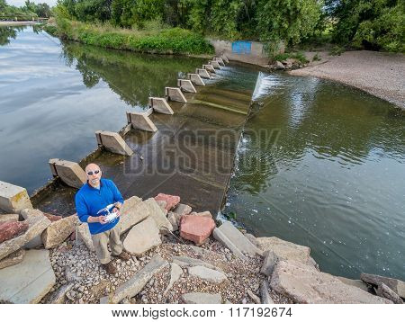 aerial view of a drone operator (pilot) on a river shore with a diversion dam