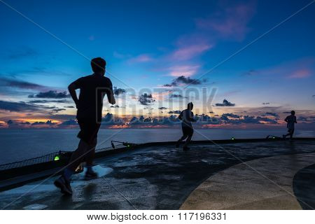 Three men running on oil and gas rig helipad in Gulf of Thailand in sunset time with helipad light on