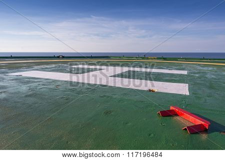 Red chock on the green oil rig helipad in Gulf of Thailand with blue sky