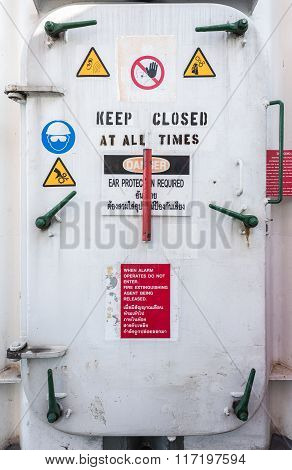 White oil rig watertight door with many handle and intruction on it in English and Thai language