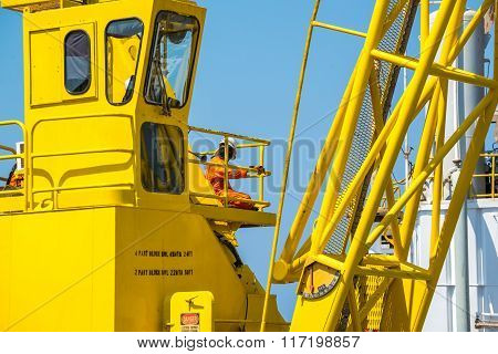 Oil rig workers working at yellow crane electic crane with crane boom up with blue sky