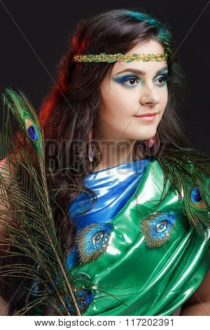 Close Up Beauty Portrait Of Beautiful Girl With Peacock Feather, Headband. Creative Makeup Peafowl