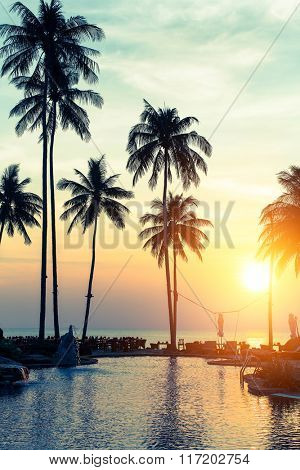 Tropical beach at amazing sunset, exotic paradise landscape with silhouettes of palm trees.