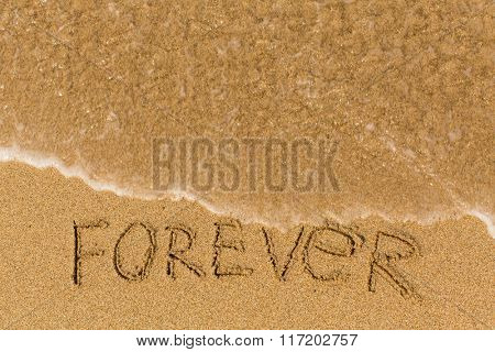 Forever - inscription on sand beach with the soft wave.