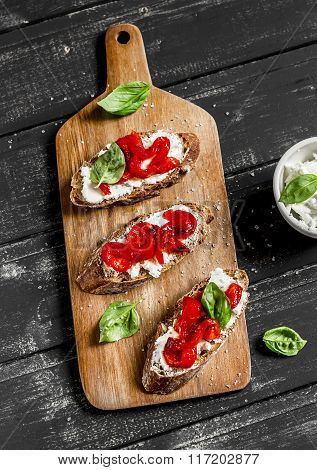 Open Sandwich Cheese, Roasted Red Sweet Peppers And Basil On A Dark Wooden Board