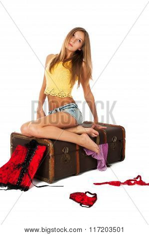 Pretty sad girl on old suitcase