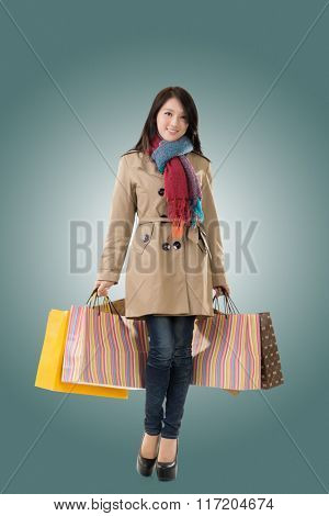 Winter shopping woman of Asian holding bags, full length portrait isolated.