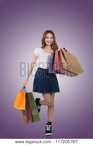 Smiling happy Asian woman shopping and holding bags, full length portrait isolated.