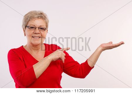 Happy Smiling Senior Female Showing Empty Hand, Copy Space For Text