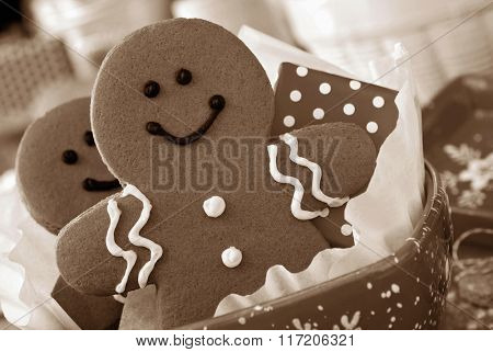 Smiling gingerbread man nestled in holiday dish with gift-wrapped surprise.  Baking supplies in soft focus in background. Sepia toned for a nostalgic feel.