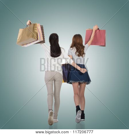 Happy smiling shopping girls of Asian holding bags with her friends. Rear view.