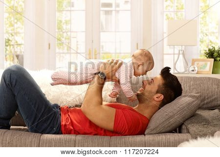 Young father playing with baby daughter on sofa. Side view.