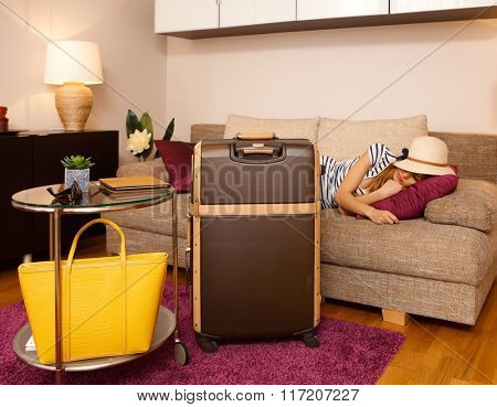 Young woman sleeping on sofa behind big suitcase before leaving apartment. Last day of holiday.