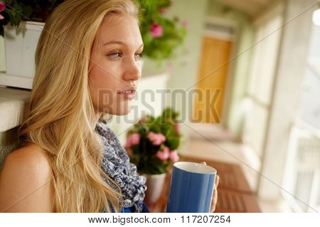 Side view of young blonde female drinking tea in balcony.