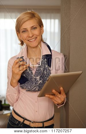 Happy young woman using tablet computer, smiling, looking at camera.