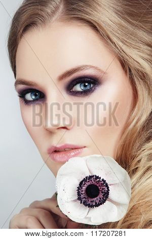 Close-up portrait of young beautiful blond woman with stylish smoky eyes make-up and fancy white flower