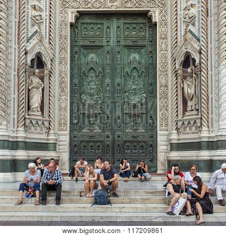 Florence, Italy - September 15, 2015: Tourist resting on the stairs in front of west door of the Duomo, Famous Santa Maria del Fiore cathedrall in Florence, Italy