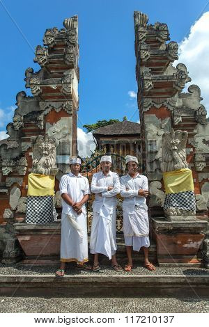 Bali, Indonesia - June 3, 2015: Balinese hindu men in traditional dress posing for photo in front of Pura Ulun Danu temple on a lake Beratan on Bali, Indonesia