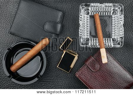 Golden Lighter With Cigar And Purse Lying On A Black Skin