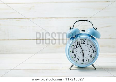Close Up Of Blue Vintage Alram Clock On White Wooden Table