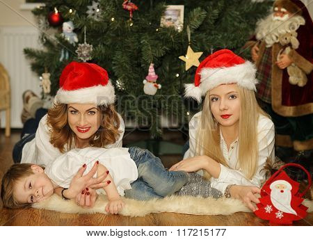 Beautiful Family In Santa Red Hats Lying Near Christmas Tree