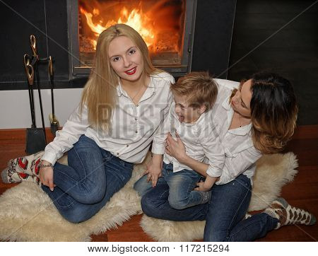 Beautiful Family Sitting On Fur Carpet Near Fireplace