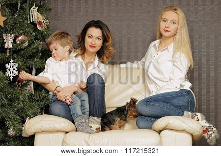Beautiful Family Sitting On The Sofa Near Christmas Tree