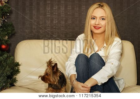 Beautiful Young Girl Sitting On The Sofa Near Christmas Tree