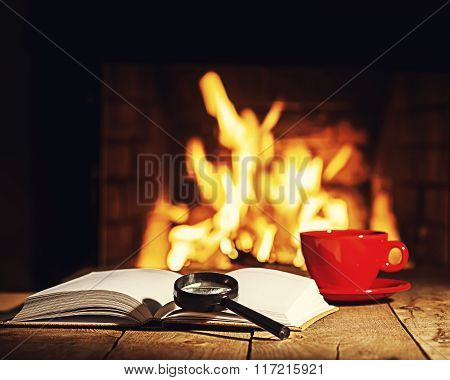 Red Cup Of Coffee Or Tea, Magnifier Glass And Old Book On Wooden Table Near  Fireplace.