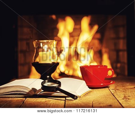 Red Cup Of Coffee Or Tea, Candle In Lamp, Magnifier Glass And Old Book On Wooden Table Near Fireplac