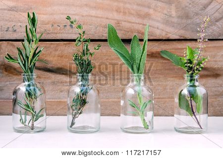 Bottle Of Essential Oil With Herbs Rosemary, Sage,holy Basil And Thyme  Set Up On Old Wooden Backgro