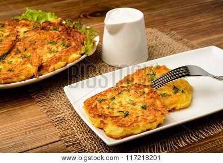 Potato pancakes on brown wooden table.