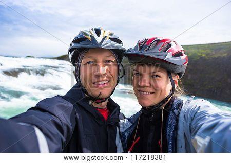 Happy couple of bikers make selfie on backdrop of Gulfoss waterfall in Iceland