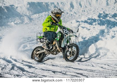 Junior rider on a motorcycle on a snowy road race