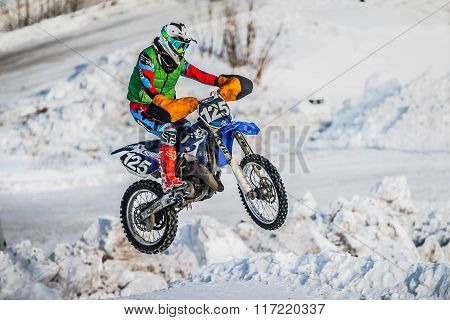 jump racer on a motorbike over snowy hill
