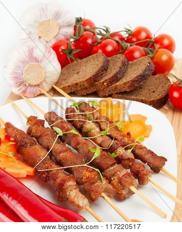 Shish Kebab With Herbs On A White Plate