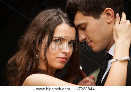 young beautiful bride hugs her fiance's neck