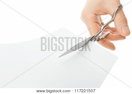 Hand With Scissors Cutting A White Sheet Of Paper