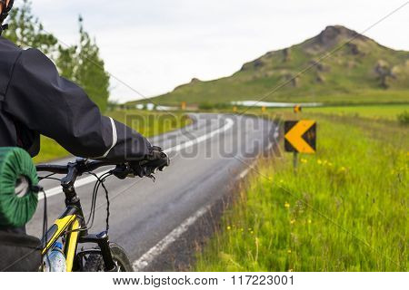 Biker rides on road at summer day in Iceland. Travel and sport picture