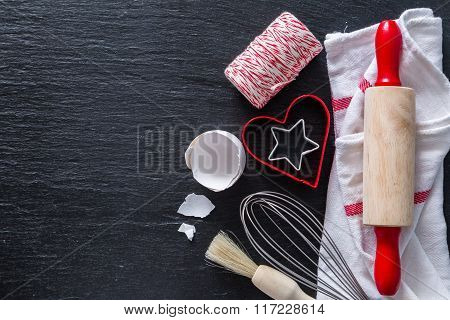 Baking concept with cooking utencils, dark stone