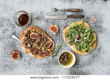 Rustic homemade pizzas with eggpant, cheese, olives, arugula, prosciutto and figs over grunge backdr