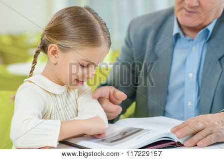 Cute granddaughter attentively exploring a book.