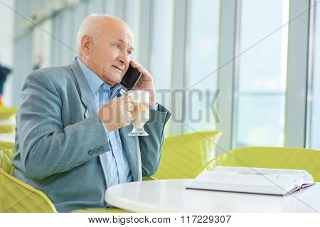 Mature good-looking man resting at the cafeteria.