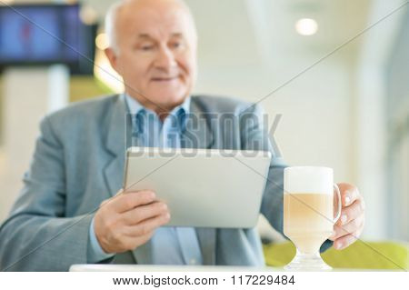 Mature man relaxing and resting at the cafeteria.
