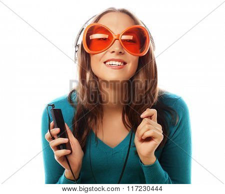 Young happy woman with headphones listening music over white background