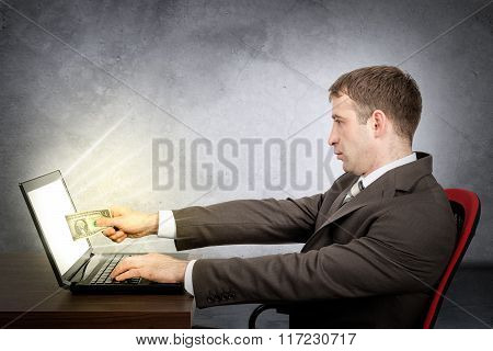 Businessman giving dollar to laptop