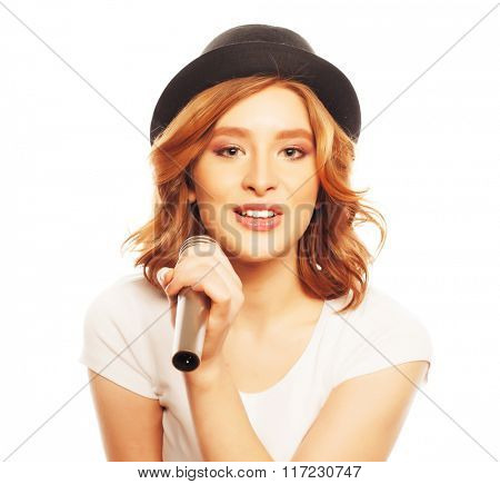 Happy singing girl. Beauty woman wearing white t-shirt and black hat with microphone over white background. Hipster style.