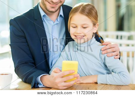 Young loving father showing adorable daughter how to use smartphone.